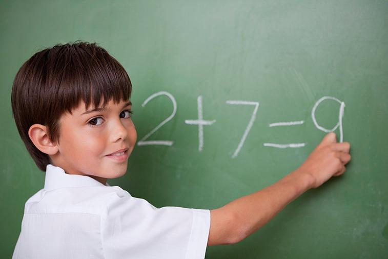 Boy doing simple math at blackboard.jpg